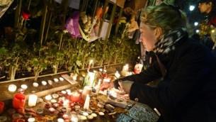 سيدة تضيء الشموع أمام نصب تذكاري مؤقت بالقرب من قاعة باتاكلان في 16 نوفمبر، 2015، في باريس. (AFP/ BERTRAND GUAY)