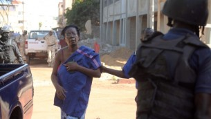 قوى الأمن المالية ترافق رهينة تم تحريرها من فندق 'رادسيون بلو, في باماكو، 20 نوفمبر، 2015. (AFP PHOTO / HABIBOU KOUYATE / AFP / HABIBOU KOUYATE)