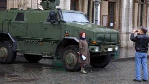 صورة تم إلتقاطها في 21 نوفمبر، 2015 يظهر فيها سياح يلتقطون صورا أمام مدرعة عسكرية بالقرب من غراند بلاس في وسط مدينة بروكسل.  (AFP PHOTO / BELGA / NICOLAS MAETERLINCK)