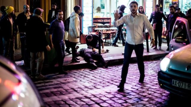 """رجل ملقى على الرصيف بالقرب من مقهى """"بون بيير"""" في باريس، في أعقاب سلسلة من الهجمات المتزامنة في باريس ومحيطها والتي أسفرت عن مقتل أكثر من 120 شخصا، 13 نوفبمر، 2015. (AFP/Anthony Dorfmann)"""