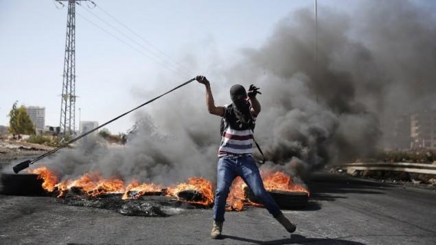 محتج فلسطيني يستخدم مقلاعا لرمي الحجارة باتجاه القوات الإسرائيلية خلال مواجهات في بيت إيل بالقرب من مدينة رام الله بالضفة الغربية، 11 أكتوبر، 2015. (AFP/Abbas Momani)