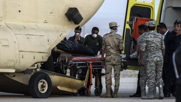 طواقم اسعاف مصرية تحمل جثامين ركاب الطائرة الروسية التي تحطمت في سيناء داخل طائرة عسمرية في قاعدة كبريت الجوية، 31 اكتوبر 2015 (KHALED DESOUKI / AFP)