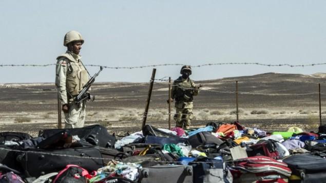 جنود مصريون يقفون بجانب أمتعة وحقائب مسافري طائرة A321 المنكوبة في موقع تحطم الطائرة في وادي الظلمات، وهي منطقة جبلية في شبه جزيرة سيناء، 1 نوفمبر، 2015. (AFP PHOTO / KHALED DESOUKI)