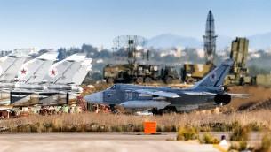 طائرة حربية روسية من طراز سو-24 في قاعدة جوية عسكرية بالقرب من اللاذقية، مع نظام دفاع صاروخي من طراز اس-400 في الخلفية (Russian Defense Ministry Facebook)