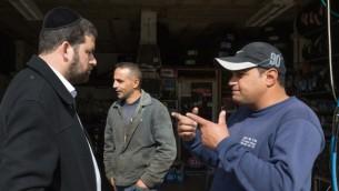 رجل يهودي متشدد من مستوطنة بيطار عليت يتحدث مع فلسطينيين اثناء غسل سيارته في الضفة الغربية، 11 نوفمبر 2015 (Nati Shohat/Flash90)