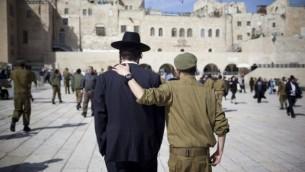 جندي ورجل حاريدي، جنيا إلى جنب. (Yonatan Sindel/Flash90)