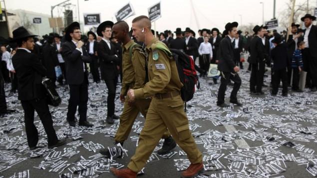 جنديان إسرائيليان يمران أمام يهود حاريديم يستعدون لمظاهرة ضخمة ضد خطط لفرض الخدمة العسكرية، 2 مارس، 2014. (Yonatan Sindel/FLASH90)