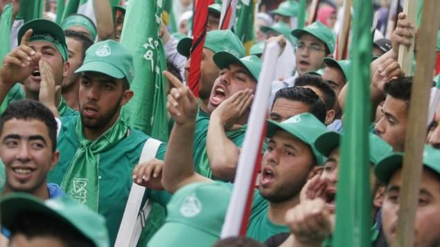 مناصرون فلسطينيون لحركة حماس يشاركون في مسيرة عشية إنتخابات مجلس الطلبة في جامعة بير زيت، في ضواحي مدينة رام الله، الثلاثاء، 6 مايو، 2014. (Issam Rimawi/Flash90)