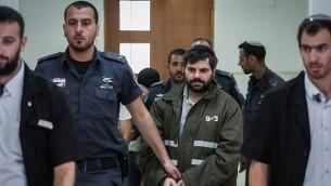 رجال الشرطة يرافقون يوسف بن دافيد، أحد المشتبه بهم اليهود في قتل المراهق محمد ابو خضير، في المحكمة المركزية في القدس، 8 يونيو 2015 (Hadas Parush/Flash90)