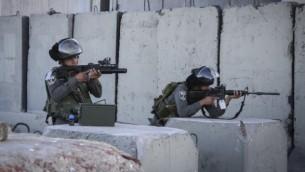 عناصر من شرطة حرس الحدود عند حاجز قلنديا بالقرب من مدينة رام الله بالضفة الغربية، 30 يونيو، 2015. (STR/Flash90)