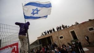 """محتجون يقفون على سطح كنيس """"أييليت هشاحر"""" في مستوطنة """"جفعات زئيف"""" بالضفة الغربية، شمال القدس، 4 نوفمبر، 2015. (Yonatan Sindel/Flash90)"""