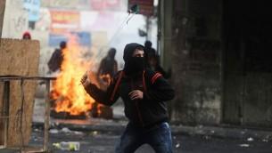 محتجون فلسطينيون يستخدمون المقاليع لإلقاء الحجارة باتجاه القوات الإسرائيلية خلال إشتباكات في مدينة الخليل بالضفة الغربية، 5 نوفمبر، 2015. (by Flash90)