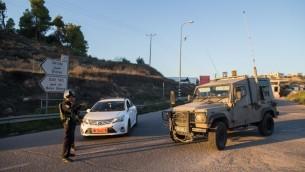 """القوات الإسرائيلية بالقرب من مفرق """"عوتنئيل"""" حيث قُتل رجل إسرائيلي وابنه (18 عاما) وأُصيب 5 آخرون في هجوم وقع جنوب مدينة الخليل بالضفة الغربية، 13 نوفمبر، 2015. (Yonatan Sindel/Flash90)"""