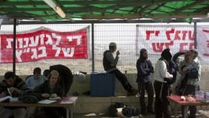 """نشطاء من اليمين في كنيس 'أييليت هشاحر' في مستوطنة 'غيفعات زئيف' بالضفة الغربية، يجلسون أمام لافتات كُتب عليها """"أوقفوا تمييز المحكمة العليا""""، 16 نوفمبر، 2015. (Lior Mizrahi/Flash90)"""