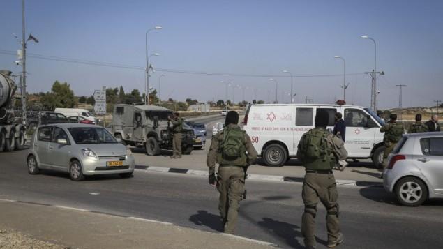 قوات الأمن الإسرائيلية في موقع هجوم قام خلاله سائق فلسطيني بدهس جنود إسرائيليين بالقرب من بيت أمر في الضفة الغربية، 27 نوفمبر، 2015. (Photo by Gershon Elinson/Flash90)