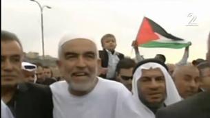 رئيس الفرع الشمالي للحركة الإسلامية في إسرائيل رائد صلاح (في الوسط) وعضو الكنيست جمال زحالقة (من اليسار)خلال تظاهرة في 28 نوفمبر، 2015. (لقطة شاشة: القناة 2)