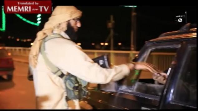 """لقطة شاشة من شريط فيديو نشره معهد """"ميمري"""" يظهر مقاتلا من تنظيم """"الدولة الإسلامية"""" يقوم بتوزيع الحلوى على السائقين للإحتفال بتحطم الطائرة الروسية في 31 أكتوبر، 2015. (MEMRI)"""