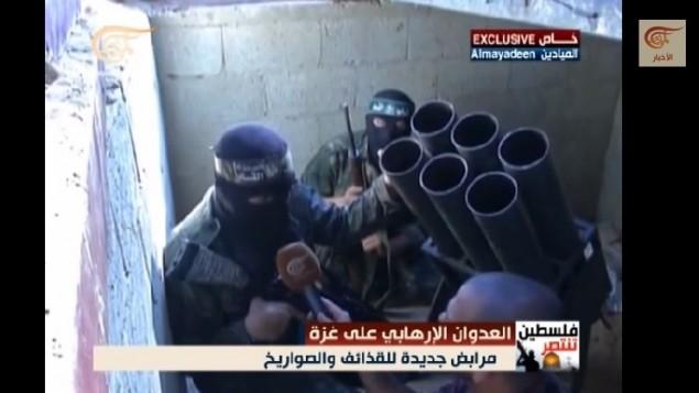 """في صور إلتقطتها قناة """"الميادين""""، يظهر مقاتلون من كتائب عز الدين القسام التابعة لحركة حماس وهم يجهزون صواريخا لإطلاقها ضد إسرائيل في نفق تحت قطاع غزة، أغسطس 2014. (لقطة شاشة، YouTube)"""