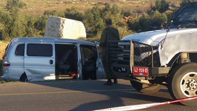 قوات الأمن الإسرائيلية في موقع الهجوم الدامي الذي وقع بالضفة الغربية في 13 نوفمبر، 2015. المركبة الإسرائيلية التي تم إطلاق النار عليها ما أدى إلى مقتل أب وإبنه تظهر في الخلفية (لقطة شاشة: القناة 2)