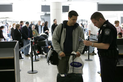 ضابط جمارك يقوم بفحص جواز سفر أحد المسافرين بعد وصوله إلى مطار واشنطن دالاس الدولي (صورة توضيحية:James Tourtellotte/ Department of Homeland Security)