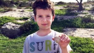 إيتاي هالبرين، 8 أعوام، ورأس تمثال من العصر الحديدي عثر عليه خلال تجوله بالقرب من تل بيت شيمش. (Arik Halperin, courtesy of Israel Antiquities Authority)