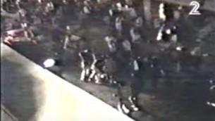 لقطة شاشة من شريط فيديو مصور هاو يظهر الحراس الشخصيين ورجال الشرطة يهمون بالقفز على قاتل يتسحاق رابين، ييغال عامير، في تل أبيب، 4 نوفبمر، 1995. (لقطة شاشة: عبر YouTube)