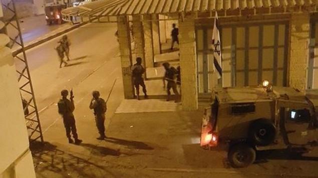 """هذه الصورة نشرها مستخدمون على مواقع التواصل الإجتماعي الفلسطينية ليلة السبت تظهر كما يُزعم جنودا إسرائيليين خارج مكاتب إذاعة """"دريم"""" في الخليل. (لقطة شاشة: Facebook)"""