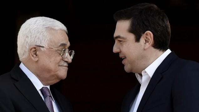 رئيس الوزراء اليوناني الكسيس تسيبراس يرحب بالرئيس الفلسطيني محمود عباس قبل لقائهما في اثينا، 21 ديسمبر 2015 (ARIS MESSINIS / AFP)