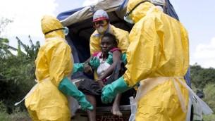 (ارشيف) عمال صحة يرتدون بزز واقية ينقلون مريضة يشتبه اصابته بمرض ايبولا في غينيا، 21 نوفمبر 2014 (KENZO TRIBOUILLARD / AFP)