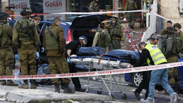القوات الإسرائيلية وخبراء الطب الشرعي يقومون بنقل جثة مازن عريبة الذي قُتل بعد إطلاق النار عليه في أعقاب هجوم عند حاجز حزكة شمال القدس، 3 ديسمبر، 2015. (AFP PHOTO / AHMAD GHARABLI) GHARABLI)