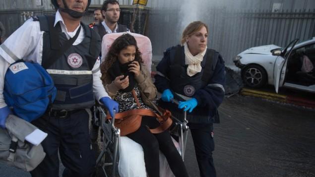 مسعفون من نجمة داوود الحمراء يقدمون المساعدة لشابة مصابة بعد قيام فلسطيني بدهس مجموعة من الأشخاص كانت تقف في محطة للحافلات في القدس، 14 نوفمبر، 2015، ما أدى إلى إصابة 14شخصا. (AFP PHOTO/MENAHEM KAHANA)