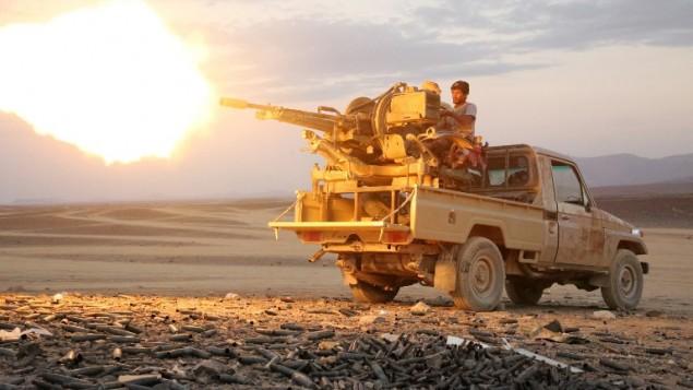 رجل قبائل يمنييين من لجان المقاومة الشعبية، التي تقدم الدعم لقوات موالية للرئيس عبد ربو منصور هادي، المدعوم من السعودية، يطلق النار من مدفع رشاش في منطقة سروة، شرقي العاصمة صنعاء، 14 ديسمبر، 2015. (AFP/ABDULLAH AL-QADRY)