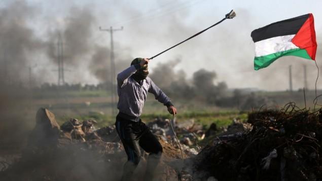 محتج فلسطينيون يلقي بحجر تجاه القوات الإسرائيلية خلال مواجهات بالقرب من منطقة الشجاعية في مدينة غزة على طول الحدود مع إسرائيل في 18 ديسمبر، 2015. (AFP PHOTO/MAHMUD HAMS)