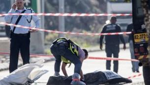 شرطي إسرائيلي يقف بجانب جثة منفذ هجوم فلسطيني الذي قُتل بعد إطلاق النار عليه بعد أن قام بطعن حارسي أمن إسرائيليين في منطقة بركان الصناعية  القريبة من مستوطنة أريئيل، 24 ديسبمر، 2015. (Phot by AFP Photo/Jack Guez)
