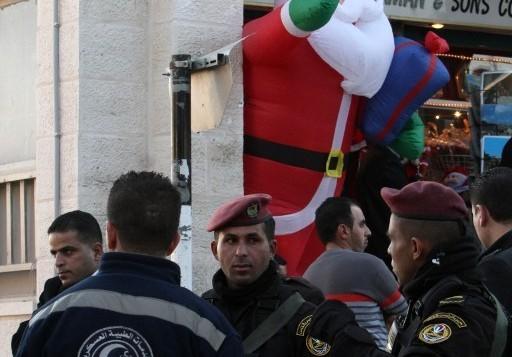 قوى الأمن والخدمات الطبية العسكرية خارج كنيسة المهد حيث يحتشد المسيحيون لإحتفالات الميلاد في مدينة بيت لحم بالضفة الغربية، 24 ديسمبر، 2015. (AFP/Musa al-Shaer)