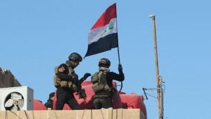 رجال جهاز مكافحة الارهاب يرفعون العلم العراقي فوق المجمع الحكومي في مدينة الرمادي بعد تحريرها من سيطرة تنظيم الدولة الإسلامية، 28 ديسمبر 2015 (AHMAD AL-RUBAYE / AFP)