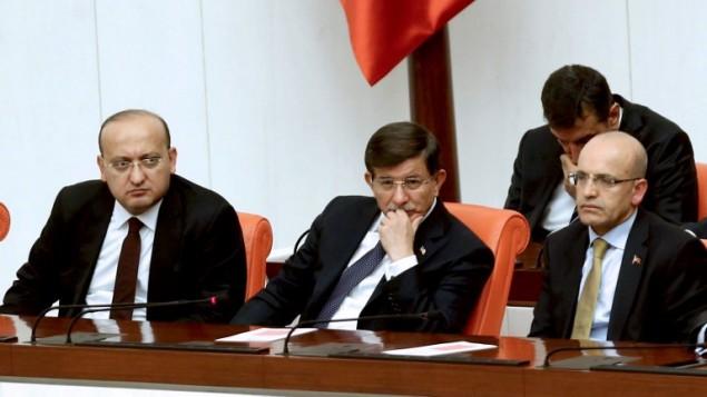 نائب رئيس الوزراء التركي محمد شيمشيك (يمين)، ورئيس الوزراء التركي محمد داود اوغلو، ونائب رئيس الوزراء التركي يالجين اكدوغان في البرلمان التركي، 28 نوفمبر 2015 (ADEM ALTAN / AFP)
