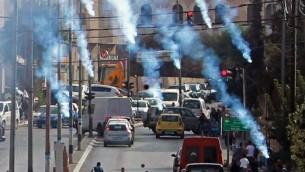 محتجون فلسطينيون يركضون للإحتماء من الغاز المسيل للدموع الذي تطلقة القوات الإسرائيلية خلال مواجهات في مدينة بيت لحم في الضفة الغربية، 2 أكتوبر، 2015. (Musa al Shaer/AFP)