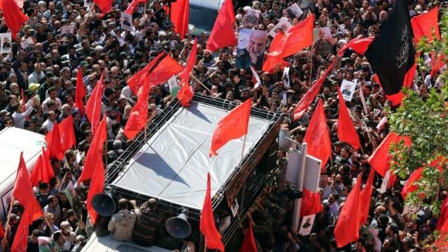 """من الأرشيف: رجال إيرانيون يحملون صورا للعميد في الحرس الثوري الإيراني حسين همداني خلال جنازته في طهران في 11 أكتوبر، 2015. العميد همداني قُتل على يد جهاديين من تنظيم الدولة الإسلامية """"خلال مهمة إستشارية"""" في منطقة حلب الشمالية، بحسب بيان صادر عن الحرس الثوري. (AFP/ATTA KENARE)"""