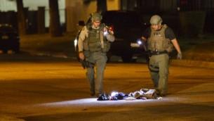ضباط شرطة يفحصون حقيبة مشبوهة في شوارع حي سان برناردينو في لوس انجليس بعد عملية اطلاق نار في مركز اجتماعي للاشخاص المعوقين، 2 ديسمبر 2015 (AFP PHOTO / PATRICK T. FALLON)