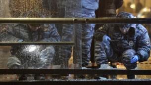 عناصر شرطة موسكو يتفحصون محطة حافلات تضررت بانفجار قنبلة يدوية، 7 ديسمبر 2015 (NATALIA KOLESNIKOVA / AFP)