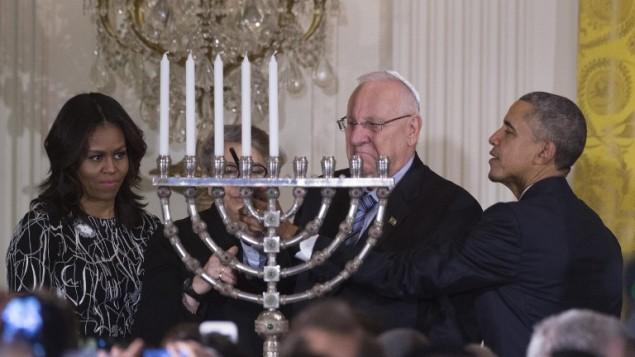 الرئيس الأمريكي باراك أوباما يساعد الرئيس الإسرائيلي رؤوفين ريفلين في إضاءة الشمعدان خلال إحتفال بمناسبة عيد الحانوكاه اليهودي في البيت الأبيض بالعاصمة واشنطن، 9 ديسمبر، 2015. (Photo by AFP Photo/Jim Watson)