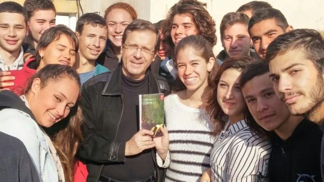 رئيس المعارضة يتسحاك هرتسوغ يتصور مع نسخة من كتاب 'جدار حي' للكاتبة دوريت رابينيان، محاط بطلاب في الكلية السابقة للجيش في سديروت، 31 ديسمبر 2015 (Courtesy Zionist Union)