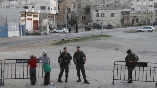 (ارشيف) مستوطنون يهود وعناصر شرطة الحدود الإسرائيلية امام ,بيت هماخبيلا' في الخليل، ابريل 2012 (Miriam Alster/Flash90)