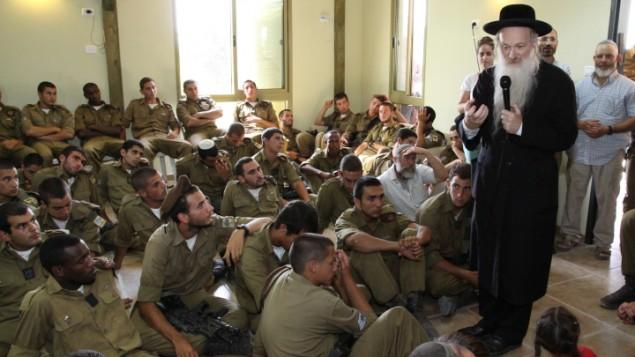 الحاخام دانييل ستافسكي يتحدث أمام جنود من لواء جولاني خلال حفل تأبيني لأبناء  المربية الإسرائيلية ميريام بيرتس، في غوش عتصيون بالضفة الغربية، 8 يوليو، 2013. (Gershon Elinson/FLASH90)