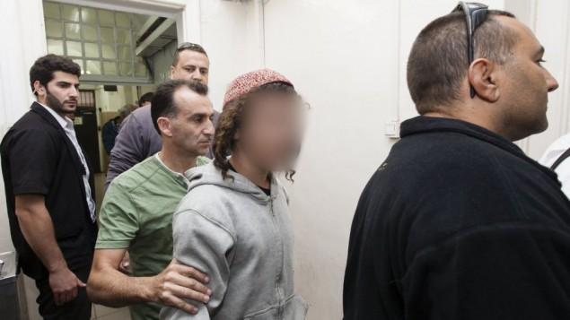 من الأرشيف: مشتبه به يهودي متطرف ترافقه الشرطة للمثول امام المحكمة المركزية في القدس بشبهة إحراق منزل في قرية سنجل بالضفة الغربية، نوفمبر 2013. (Flash90)