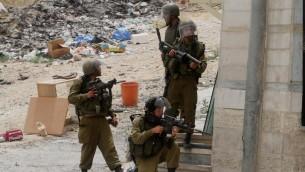 جنود اسرائيليون خلال مظاهرة في حاجز قلنديا، بالقرب من مدينة رام الله في الضفة الغربية، 5 يونيو 2014 (Issam Rimawi/Flash90)