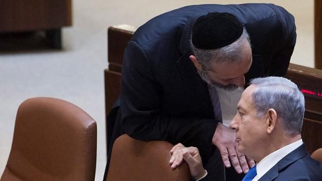 رئيس الوزراء بنيامين نتنياهو يتحدث مع رئيس حزب شاس ووزير الاقتصاد السابق ارييه درعي في الكنيست، 17 يونيو 2015 (Miriam Alster/Flash90)