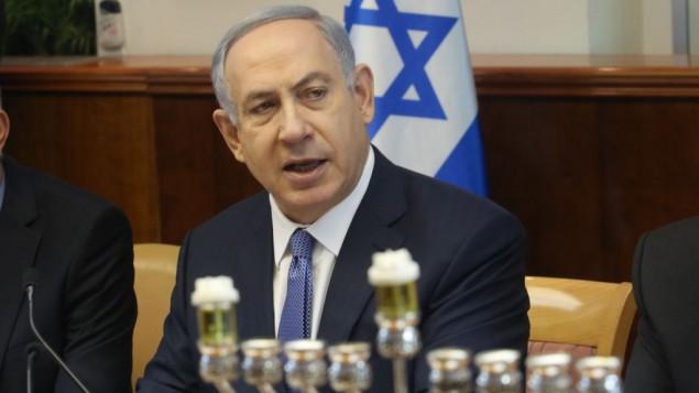 رئيس الوزراء الإسرائيلي بينيامين نتنياهو يتحدث في مستهل الجلسلة الأسبوعية للمجلس الوزراي في القدس، إلى جانب الشمعدان الجاهز لإضاءة الشمعة الاولى في عيد الحانوكاه اليهودي، 6 ديسمبر، 2015. (Emil Salman/Haaretz)