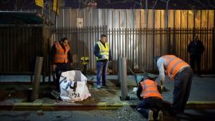 عمال إسرائيليون وفلسطينيون يقومون بوضع حواجز في محطة حافلات في القدس، 20 ديسمبر، 2015، بعد هجوم وقع في الأسبوع الماضي. (Yonatan Sindel/Flash90)